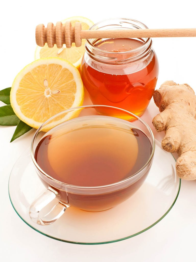 Tea in glass cup with honey, lemon and ginger